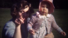 1949: Mother waving baby arm in classic pink bonnet hat. Stock Footage
