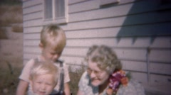 1949: Blonde baby brothers playing with grandma with corsage. - stock footage