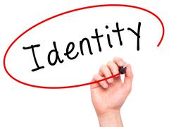 Man Hand writing Identity with black marker on visual screen Stock Photos
