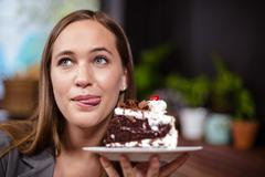 Sweet tooth woman holding piece of cake - stock photo