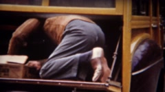 1943: Man getting axe out of woody station wagon car trunk. Stock Footage