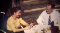 1943: Women dealing playing cards with husband at outdoor cabin. Stock Footage