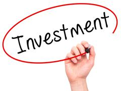 Man Hand writing Investment with black marker on visual screen - stock photo