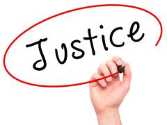 Man Hand writing Justice with black marker on visual screen Stock Photos