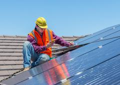 Stock Photo of worker and solar panels