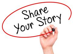 Man Hand writing Share Your Story with marker on transparent wipe board - stock photo