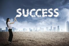 Business person spraying bottle of aerosol create word success Stock Photos