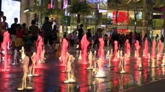 Colorful fountain and people in front Siam Paragon Mall. Bangkok, Thailand Stock Footage