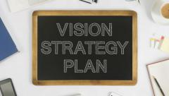 Writing vision, strategy and plan on a chalkboard at office desk - stock footage