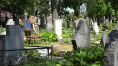 Stock Video Footage of Sorrow woman shrink near father husband tomb in graveyard. 4K
