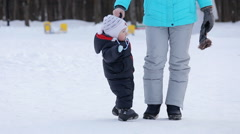 Young mother walking in Park with child, winter day Stock Footage