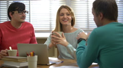 Coffee-break. Young people drinking coffee and talking in office. Slow motion. Stock Footage
