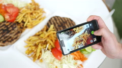 Man take a photo picture of food via his smartphone and view gallery Stock Footage