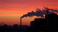 Rubber products plant emitting steam during red sunset - stock footage