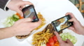 Friends take a photo picture of food via two smartphone above a dish Footage