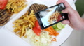 Man take a photo picture of food via his smartphone above a dish Footage