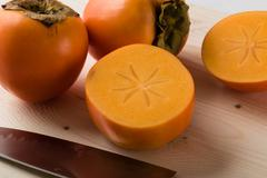 Persimmons on cuttingboard Stock Photos