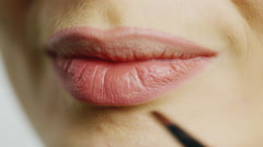 Apply lipstick on the lips of young woman Stock Footage