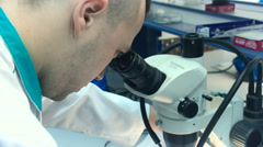 a Man in a White Coat Looking Into a Microscope in the Lab Closeup - stock footage