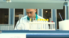 Man in a White Coat in the Chemistry Lab Doing Science - stock footage