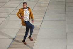 Black male fashion model posing outdoors in casual clothes - stock photo