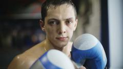 Portrait of strong man kickboxer doing self-defense and looking at camera - stock footage