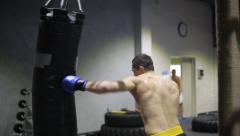 Sports: Man is practicing kick in a boxing gym Stock Footage