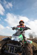 Boy rides on electric ATV quad. - stock photo