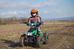 Boy rides on electric ATV quad. Stock Photos