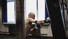 Sports: Man is practicing kick in a boxing gym - stock footage