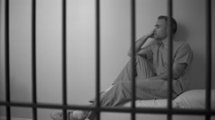 Black and white View of a sad inmate reclining on bed in prison - stock footage