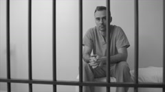 Black and white view of somber inmate sitting on bed in prison - stock footage