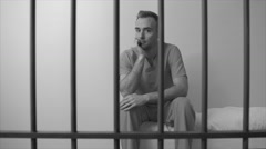 Black and white view of mournful inmate sittting on bed in prison - stock footage
