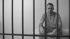 Black and white view of fuming inmate in prison stares down camera - stock footage
