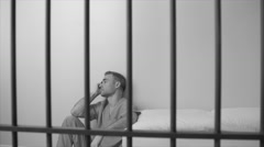Black and white view of scene of a morose inmate in prison - stock footage