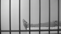 Black and white view of scene of an inmate sleeping in prison - stock footage