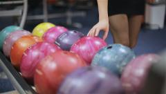 Woman takes bowling ball. Close up - stock footage