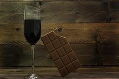 Red wine glass and bitten chocolate bar Stock Photos