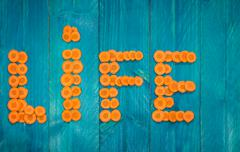 The word life written with carrot slices on blue wooden background - stock photo