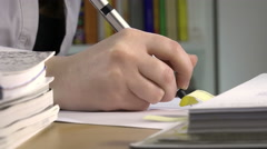 handwriting between books and notebooks: businesswoman or student  hand with pen - stock footage