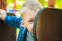 Close up portrait of funny smiling child face hiding behind slide at playground Stock Photos