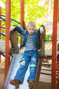 Funny sad child playing aloneoutside on children slide - stock photo