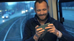 Young man playing game on smartphone during tram ride Stock Footage