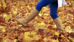 Slowmotion woman´s legs kicks to the heap of autumnal leaves Stock Footage