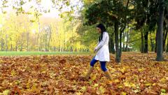 Slowmotion woman goes in park and kicks to the heap of autumnal leaves Stock Footage