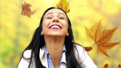 Slowmotion young beautiful happy woman throw autumnal leaves around - detail  Stock Footage