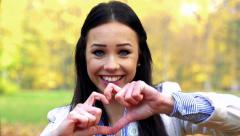 Slowmotion young beautiful happy woman stands and shows a symbol of heart  Stock Footage