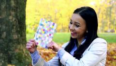 Slowmotion young beautiful happy woman stands in forest, shows a book and smiles Stock Footage