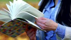 Slowmotion detail of woman who browses through the book Stock Footage