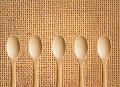 wooden spoons on sackcloth background - stock photo